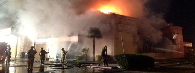 Firefighters with fire engulfed building