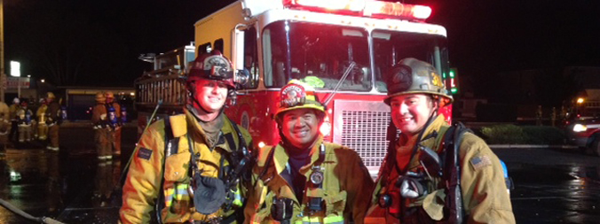 Three firefighters in front of emergency vehicle