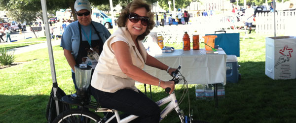 Supervisor Gonzales on a bicycle at the ARMC Health and Safety Fair